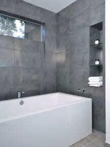 Modern bathroom idea in houston with a freestanding tub and gray tile