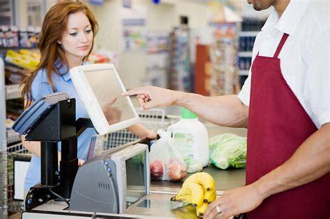 supermarket cashier ringing up purchase by locke stocksy united