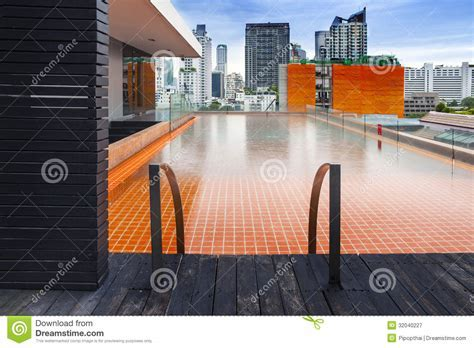 Orange Swimming Pool On Rooftop With Modern Buildi Royalty