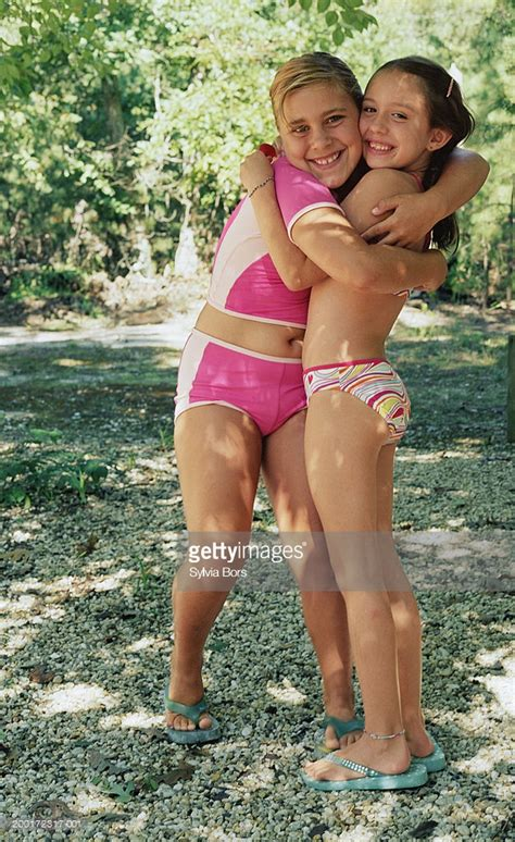 pimpandhost com young two girls in swimsuit embraced smiling portrait photo