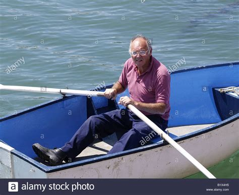 old man on boat old man in a rowing boat stock photo 18399393 alamy