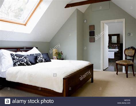 stanza da letto antica tappeto color crema e copertura per il letto in mansarda