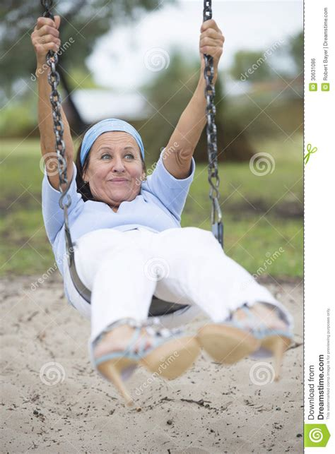 swinging old lady funny sexy senior woman on swing outdoor royalty free