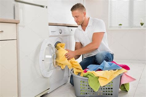 Man Putting Dirty Clothes Into The Washing Machine Stock Where To Put Laundry