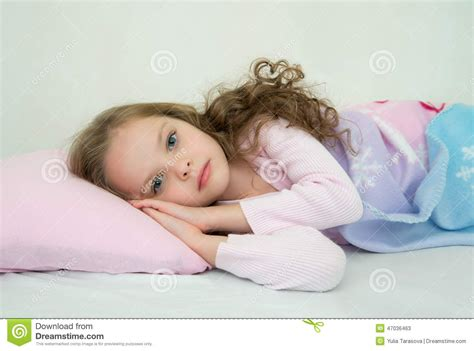 how to get her in bed adorable little girl sleeping in her bed stock photo