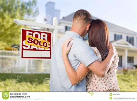 looking for a house sold for sale sign with military couple looking at house