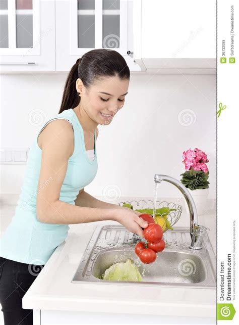 health washing and a kitchen update healthy girl s kitchen beautiful woman washing vegetables royalty free stock