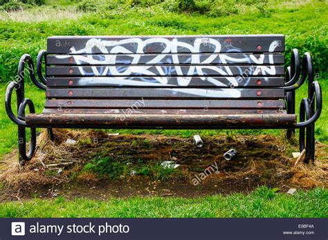 benching graffiti an empty park bench with graffiti and empty beer cans
