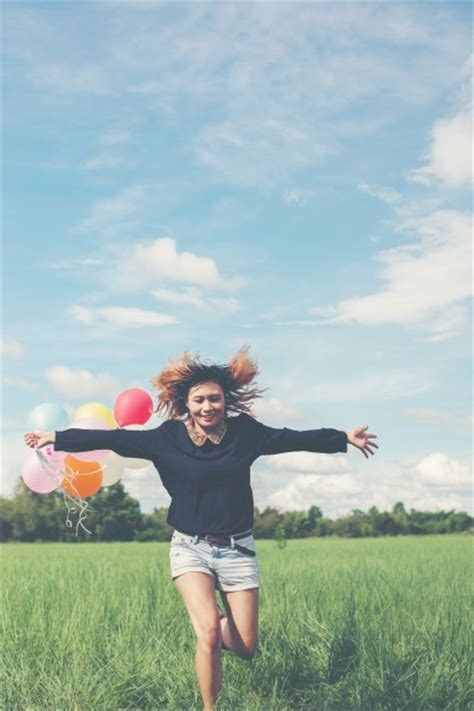 commercial girl running girl running with colores balloons in the field photo