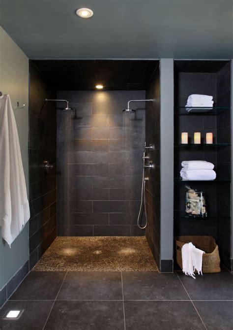 doorless curbless tile shower with river rock floor and curbless shower with small rock looking floor shower