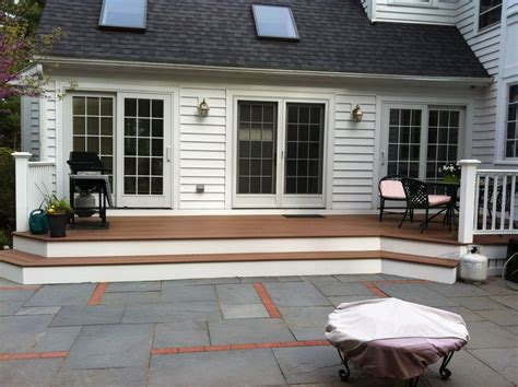 wrap around porch steps to door covered deck and open decks and fences as a part of landscape design