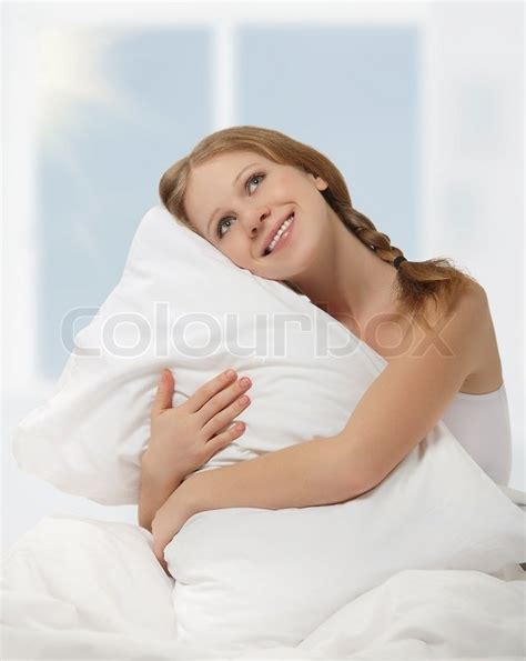 sitting in bed pillow happy dreamy beauty girl hugging a pillow while sitting in