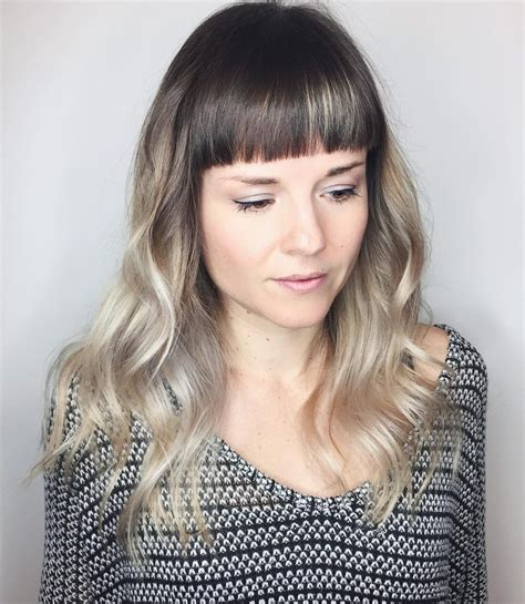 women s strawberry blonde shag with undone textured waves women s polished wavy layered cut with blunt baby bangs