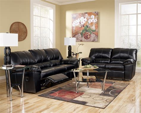 leather sofa with folding foot rest plus glass table on the colorful rug completed with floral