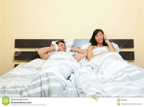 wife in bed wife phone in bed with frustrated husband stock photo