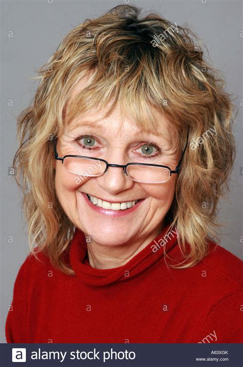 sixty year old face smiling sixty year old woman wearing glasses stock photo