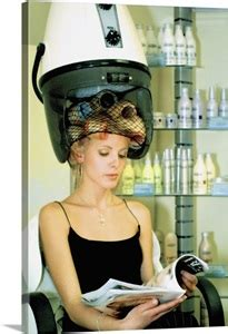 in curlers under dryer mid adult woman with rollers in her hair under a hair
