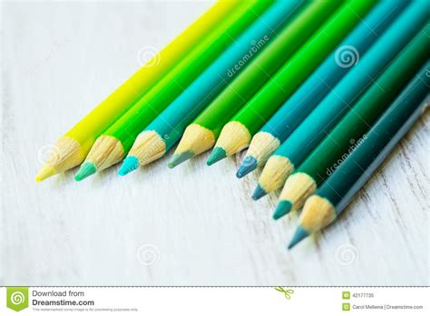 green colored blue and green colored pencils in a row stock image