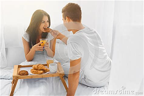 how to romance a woman in bed young man feeding woman in bed stock photo image 61076267