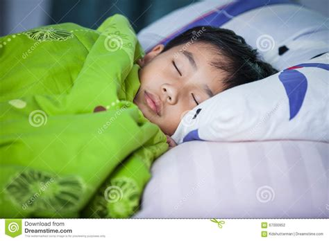 sleeping in asia healthy child little asian boy sleeping peacefully on bed