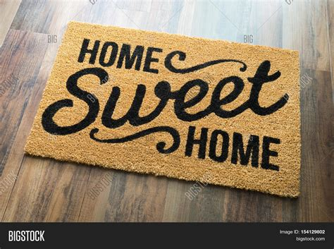 home sweet home welcome mat on wood floor stock photo
