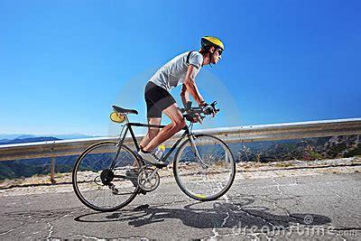 cyclist riding  bike uphill stock image image