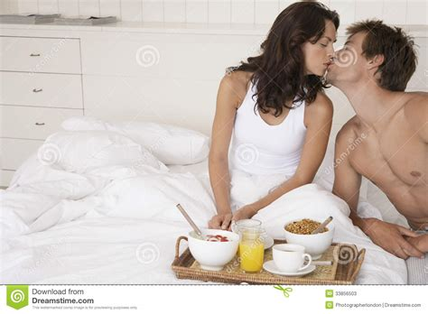 romantic pictures of couples in bed couple kissing by breakfast tray in bed stock photos