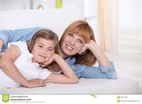 little girls sofa smiling woman and little girl on a sofa stock photos