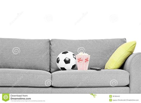 couch ball studio shot of a couch with soccer ball and popcorn box on