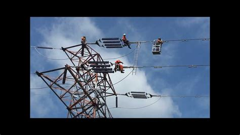 high voltage power high voltage power line workers and helicopter in