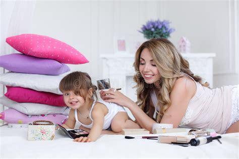 hija se mete a la cama de su padre para cpjer madre e hija que hacen el maquillaje que se sienta en la