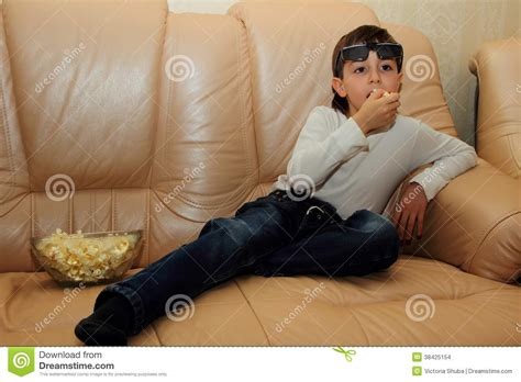 boy on couch boy sitting on a sofa with popcorn and watching tv with