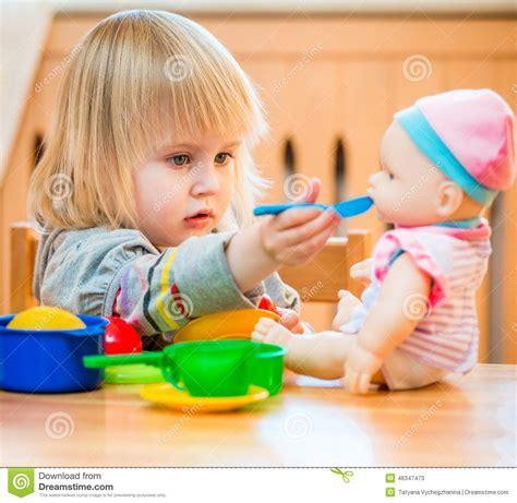 girl feeding  doll stock image image  food lovely