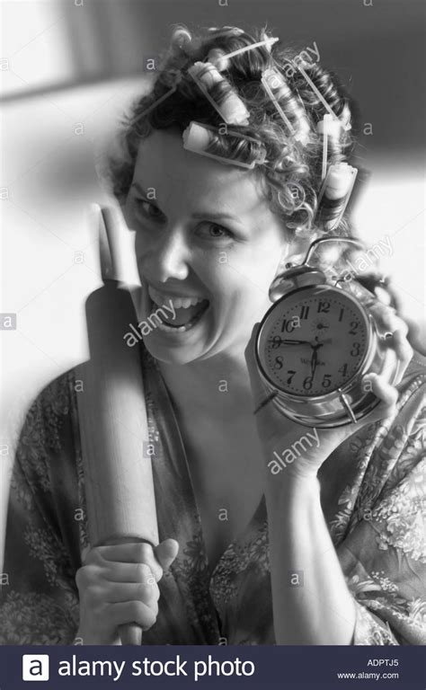 husband with long hair in curlers woman in hair curlers with rolling pin and alarm clock