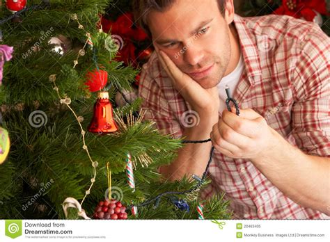 how to fix xmas lights on tree young man fixing christmas tree lights royalty free stock