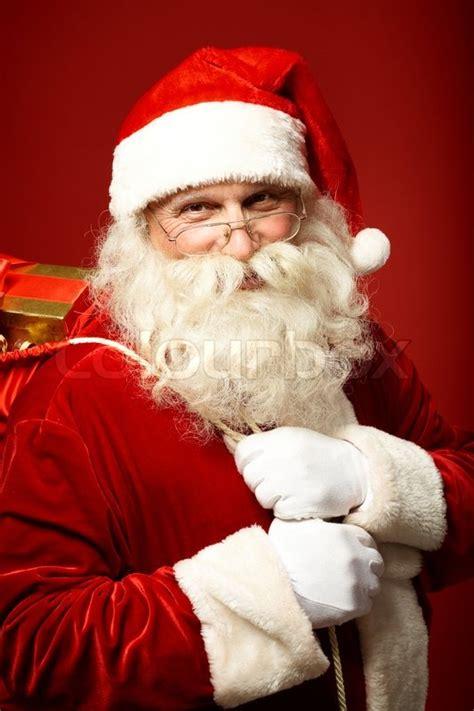 portrait  happy santa claus holding sack  gifts    camera stock photo