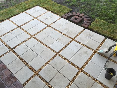 diy square paver patio almost done paver patio diy 12x12 pavers with gravel between them i put some gravel