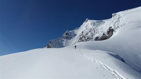 man walking in white mountain snow during daytime 183 free stock photo