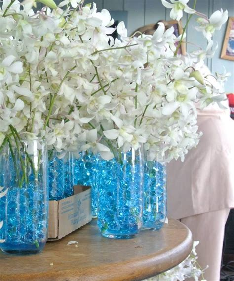 water centerpieces white orchids centerpiece blue water glass cups