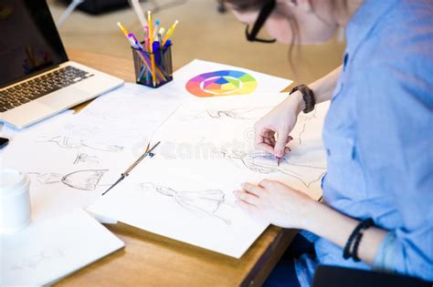 fashion illustration courses toronto creative fashion designer in glasses sitting and drawing sketches stock illustration