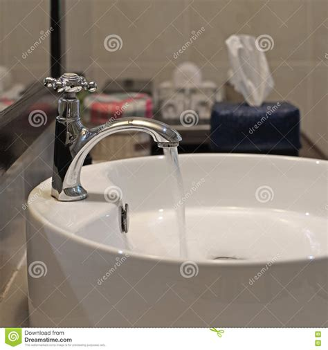 water from bathroom sink ceramic washbasin and metal faucet stock photo image