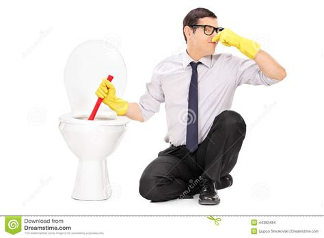 stinking up the bathroom young man unclogging a stinky toilet with plunger stock