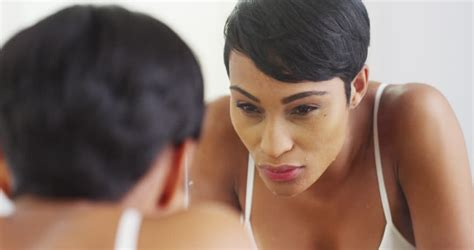 black woman looking in mirror a man lathers his face with soap to wash it in the mirror