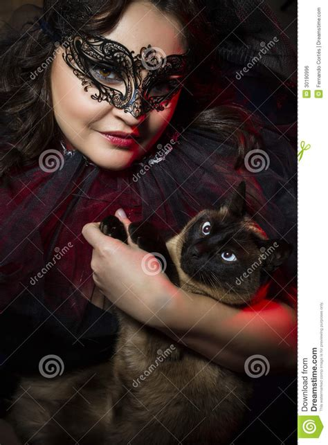 woman  siamese cat wearing venetian mask stock photo