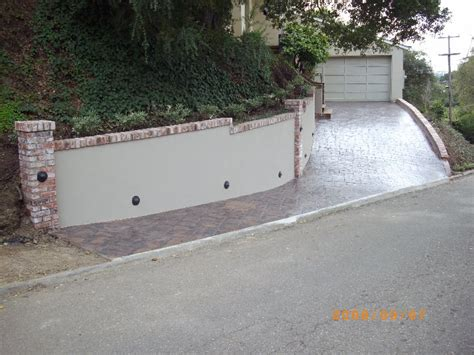 new concrete retaining wall with brick columns the new driveway has a sted finish yelp