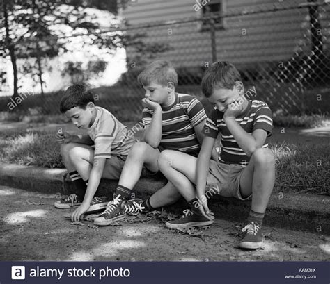 1970s Three Bored Boys Sitting On Curb All Wearing Striped Tee Shirts Stock Photo 12657925 Alamy