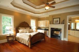 An elegant master bedroom with rich red hardwood floors a dual sided