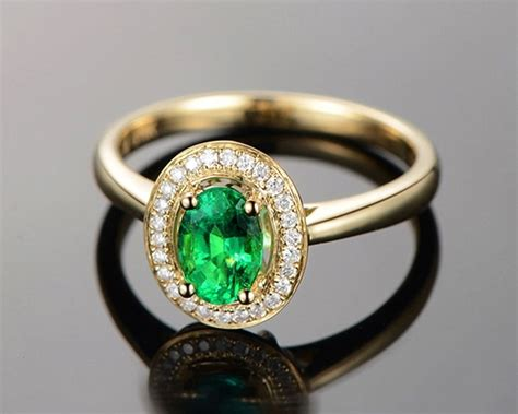 1 carat emerald and halo engagement ring in yellow