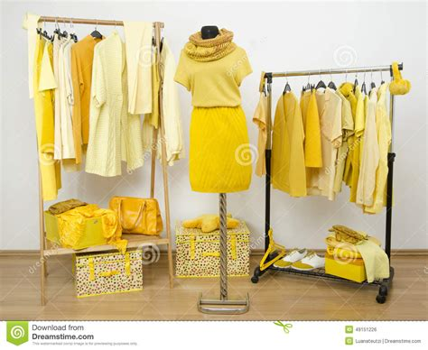 dressing closet with yellow clothes arranged on hangers