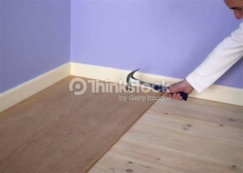 man hammering nail into plywood on top of floorboards stock photo thinkstock